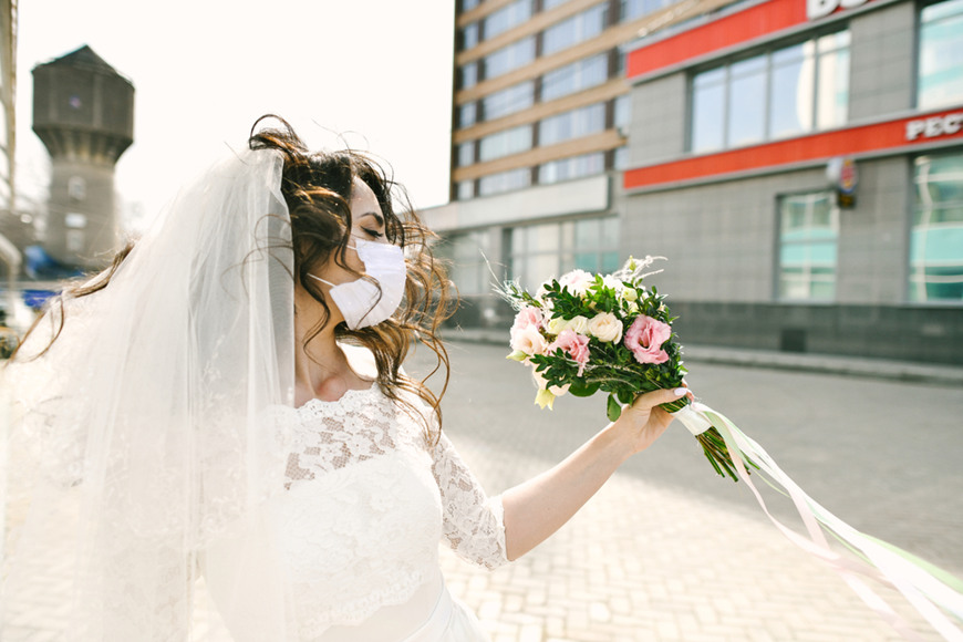 a-bride-wears-dress-and-face-mask