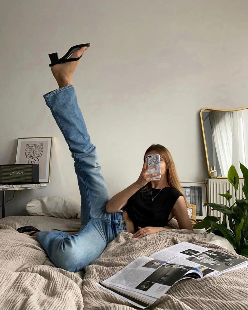 a-woman-stretches-her-leg-on-her-bed